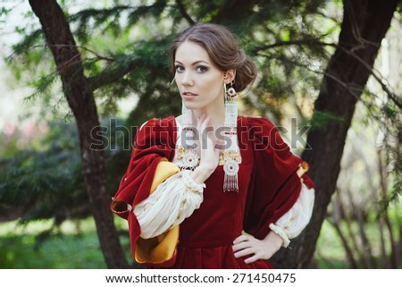 Beautiful girl in historical red dress with ear cuffs - stock photo