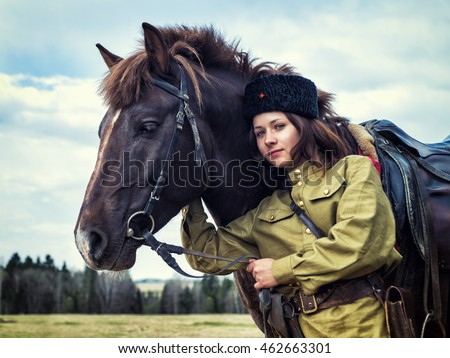 Beautiful girl in image of the soldier in Cossack uniform of the Soviet Union during the Second World War. Theatrical reconstruction.