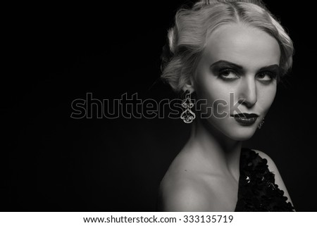 Beautiful girl in incredible dress on a dark background. Beautiful and stylish image of a girl of 20 years. Photo for fashion magazines, posters and websites.