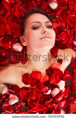 Beautiful girl in jacuzzi with rose petal. Body care. - stock photo