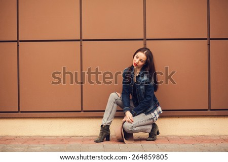 beautiful girl in jeans posing on the street. - stock photo