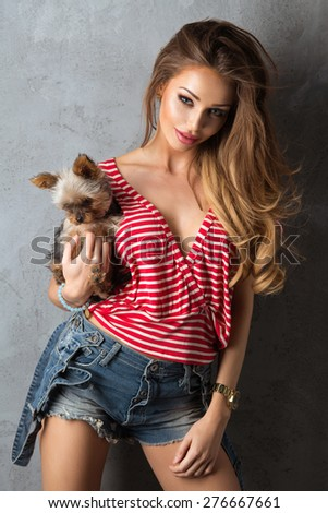 Beautiful girl in jeans shorts and a white - red shirt with dog - stock photo