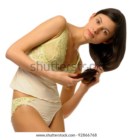 Beautiful girl in lace lingerie is combing her hair - stock photo