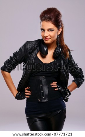 Beautiful girl in leather with headphones over gray background - stock photo