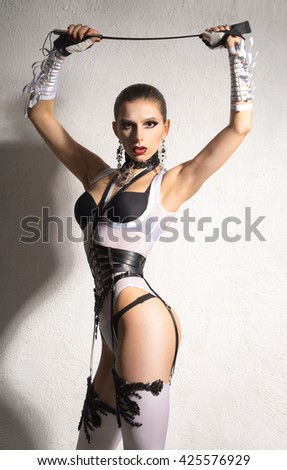beautiful girl in lingerie stands with a whip - stock photo
