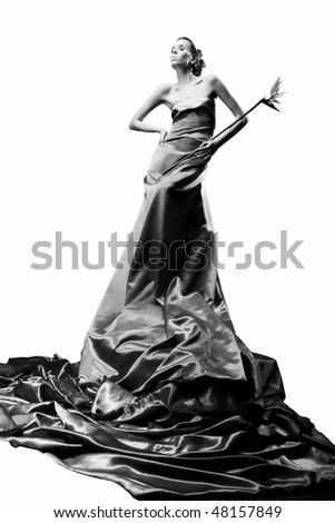 Beautiful girl in long dress holds exotic flower in hand - stock photo