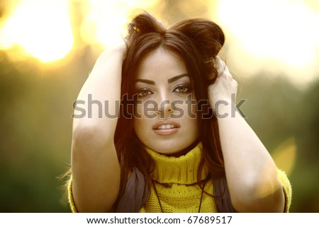 Beautiful Girl in Nature holding her hair - stock photo