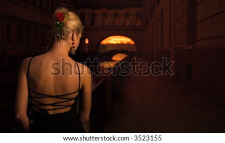Beautiful girl in old city near the river - stock photo