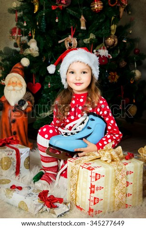 Beautiful girl in pajamas and cap is waiting Christmas and New year celebration front of X-mas tree. Old texture. - stock photo