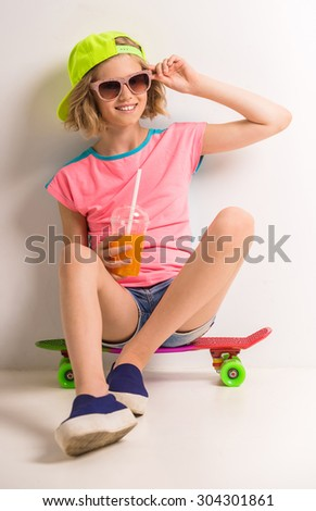 Beautiful girl in peaked cap and sunglasses holding glass of juice while sitting on skateboard against white background. - stock photo