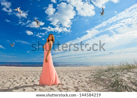 beautiful girl in pink dress on seacoast