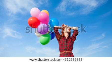 Beautiful girl in plaid dress with multicolored balloons on blue sky background - stock photo
