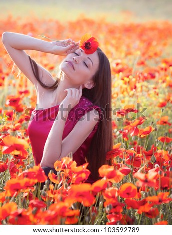 Beautiful girl in poppies meadow