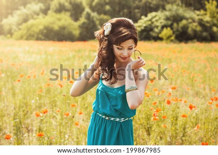 beautiful girl in poppy field in summer - stock photo