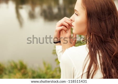 beautiful girl in profile near the lake in the summer - stock photo