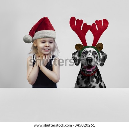 Beautiful girl in red cap of Santa Claus and dog breed Dalmatian in reindeer horns laugh and rejoice, there is a place for your text or image - stock photo