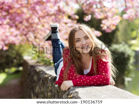 Beautiful girl in red cardigan lying on a wall in spring garden with blooming trees - stock photo