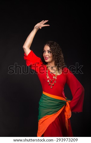 Beautiful girl in red dancing on a black background.