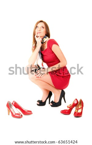 beautiful girl in red dress and in black shoes thinking wich red shoes to choose