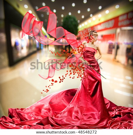 Beautiful girl in red dress background interior - stock photo