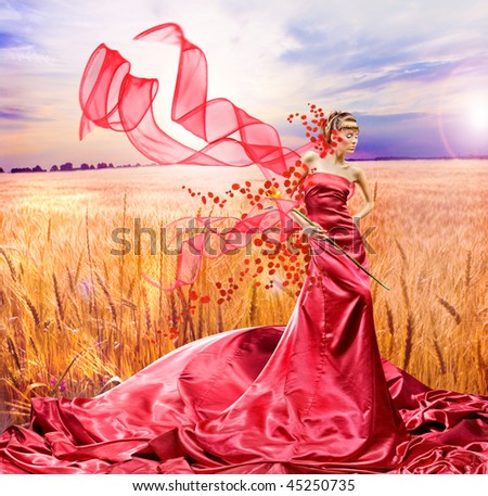 Beautiful girl in red dress. Golden wheat ready for harvest growing in a farm field - stock photo