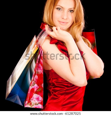 Beautiful girl in red dress is engaged in shopping, it is isolated on black background. - stock photo
