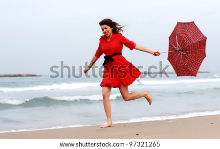 Beautiful girl in red dress on the winter beach - stock photo