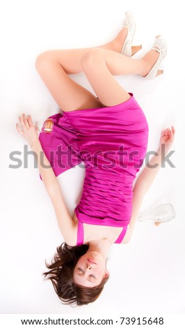 Beautiful girl in red dress sleeping with an empty glass in his hand - stock photo
