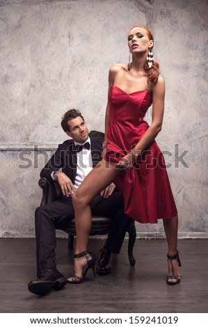 Beautiful girl in red dress trying to seduce handsome man. Showing her slender leg - stock photo