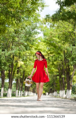 Beautiful girl in red dress walking in nature