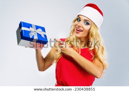 Beautiful girl in red hat of Santa, she is smiling, holding in her hand gifts, isolated on a grey background - stock photo