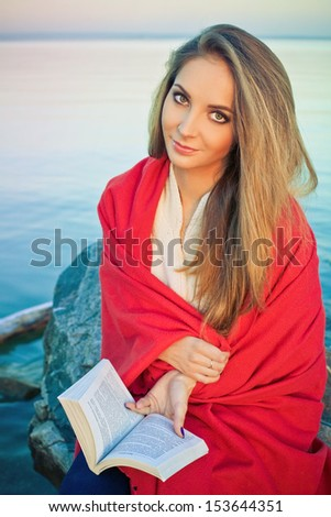 Beautiful girl in red plaid is reading a book at the beach on sunset - stock photo