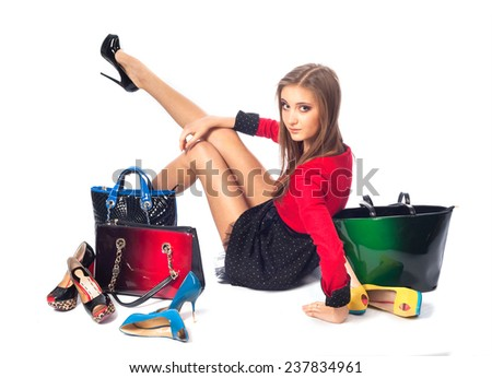 Beautiful girl in red with shoes iand bags - stock photo
