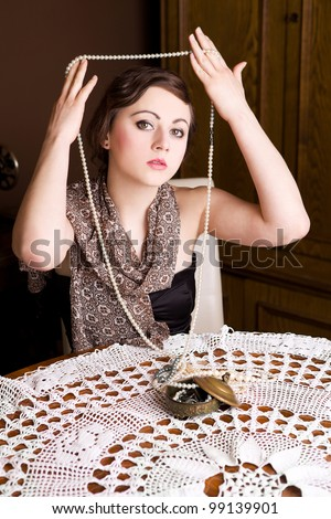 Beautiful girl in retro style with pearls. Focus on models face. Vintage shoot. - stock photo