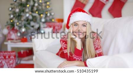 Beautiful girl in Santa Claus hat in her living room
