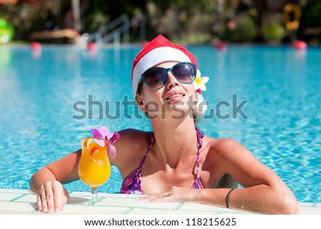beautiful girl in santa hat and sunglasses with fresh mango juice in luxury pool. christmas - stock photo