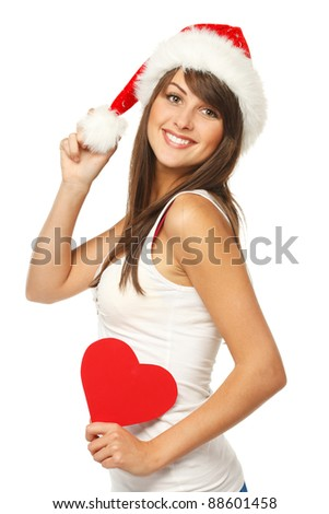 Beautiful girl in Santa hat holding heart shape - stock photo