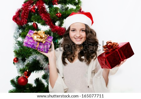Beautiful girl in santa hat near a christmas tree with gifts - stock photo