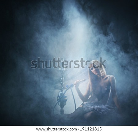 Beautiful girl in sexy underwear smoking the hookah - stock photo
