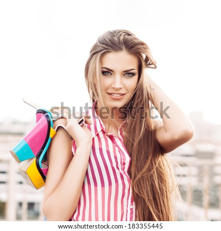 beautiful girl in sleeveless striped top messes up her long silky hair holding bright high heels - stock photo