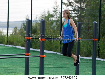 Beautiful girl in sportswear is pushed on bars. - stock photo
