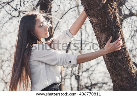 Beautiful girl in spring garden standing near by tree