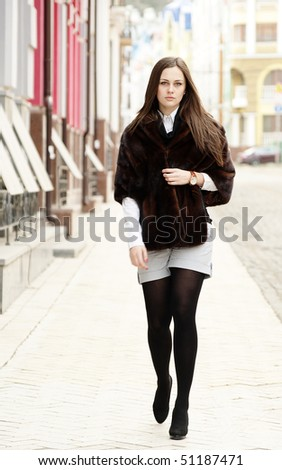 Beautiful girl in stole walking down the street - stock photo