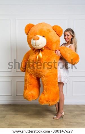 Beautiful girl in studio is holding a big teddy bear, holidays, joy, childhood. - stock photo