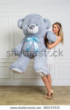 Beautiful girl in studio is holding a big teddy bear, holidays, joy, childhood. - stock photo