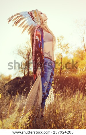 Beautiful girl in style of the American Indians dancing in the rays of the autumn sun. Western style. Jeans fashion. - stock photo