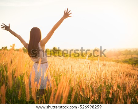 Beautiful girl in stylish summer dress walking in the field with flowers in sunlight,enjoying freedom feeling happy at sunset