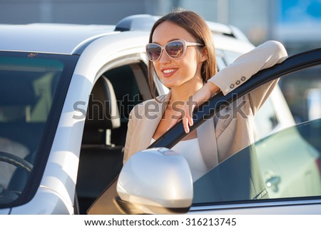 Beautiful girl in sunglasses is standing near her car. She is opening the door of vehicle and preparing to sit down in the driver seat. She is looking forward with relaxation and smiling - stock photo