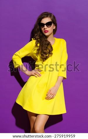 Beautiful girl in sunglasses posing in yellow mini dress. Three quarter length studio shot on violet background. - stock photo
