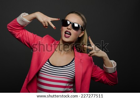 Beautiful girl in sunglasses showing thumbs up - stock photo